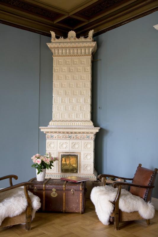 Soba din placi de terracotta alba pare a conecta parchetul de lemn si plafonul decorat cu lemn