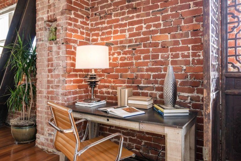 Mic birou amenajat intr-un apartament modern, cu zidaria din caramida lasata la vedere