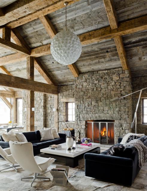 Living rustic cu pereti de piatra si grinzi de lemn la vedere