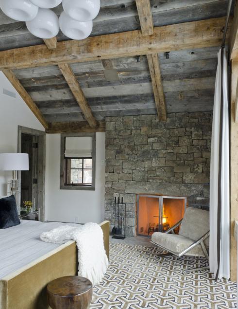 Dormitor rustic cu grinzi de lemn si zid din piatra