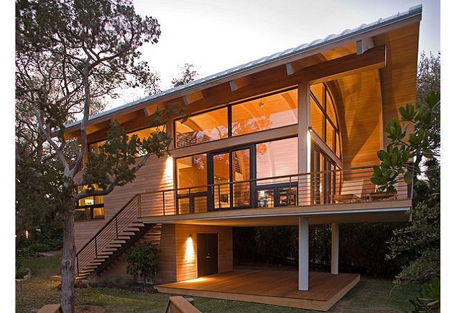 Casa din lemn si sticla cu un acoperis curbat