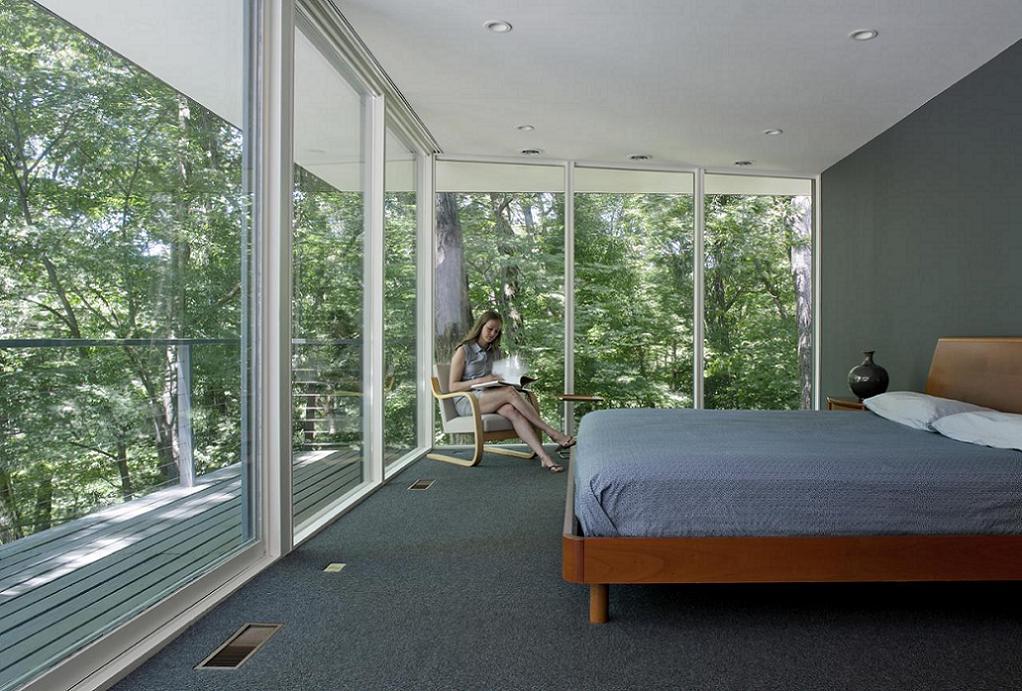 Dormitor matrimonial ce  pare a se afla in coronamentul copacilor