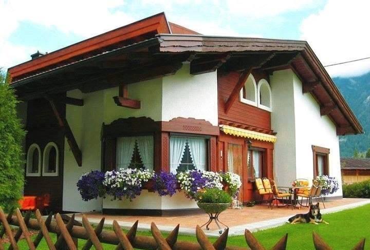 O casa frumoasa cu finisaje din lemn ce decoreaza acoperisul, geamurile si o parte a fatadei
