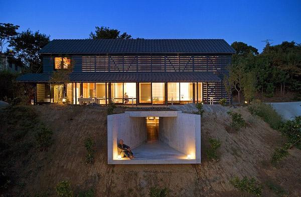 Casa cu pereti de sticla umbriti de panouri de lemn