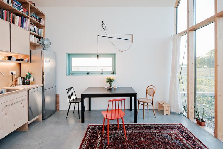 Bucataria si locul de luat masa intr-o casa familiala compacta, cu un perete in intregime realizat d