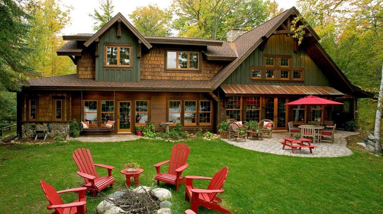 Casa din lemn cu o curte verde si fotolii rosii in jurul focului