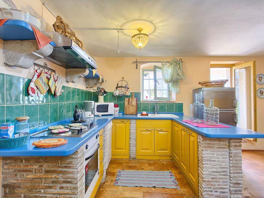 Bucatarie plina de culoare avand mobilierul inzidit si decorat cu piatra naturala