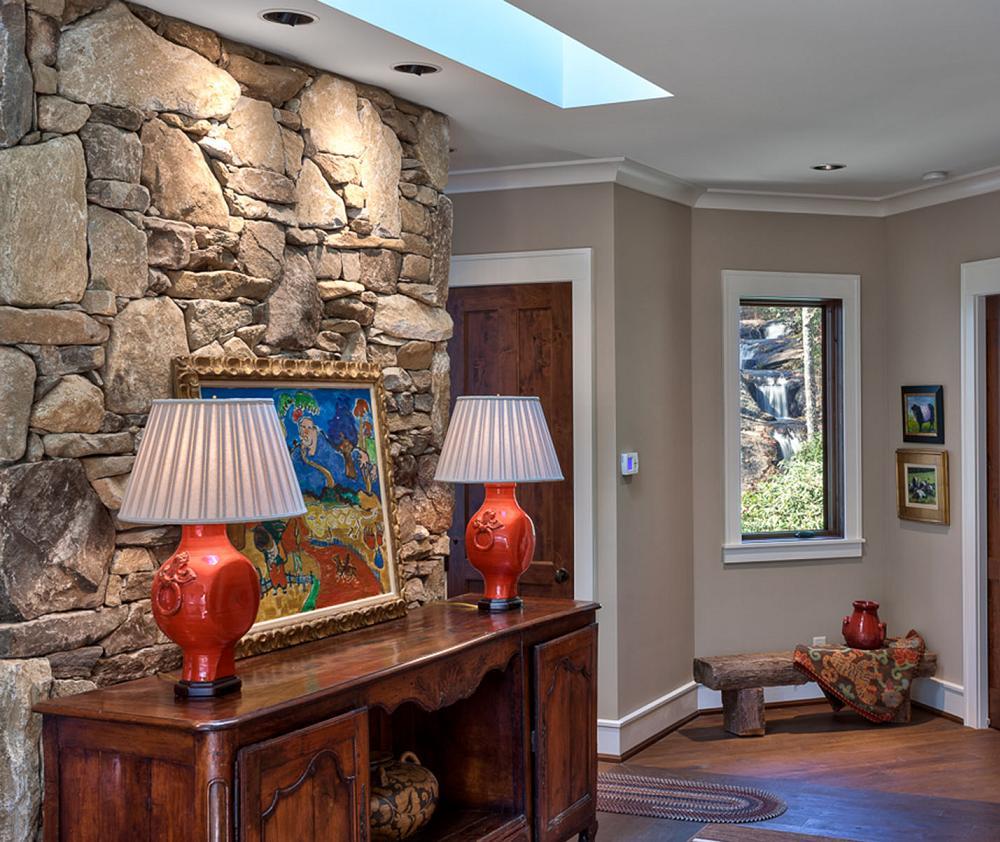 Hol amenajat rustic, cu piatra naturala si mobilier de lemn, zugravit in culori neutre