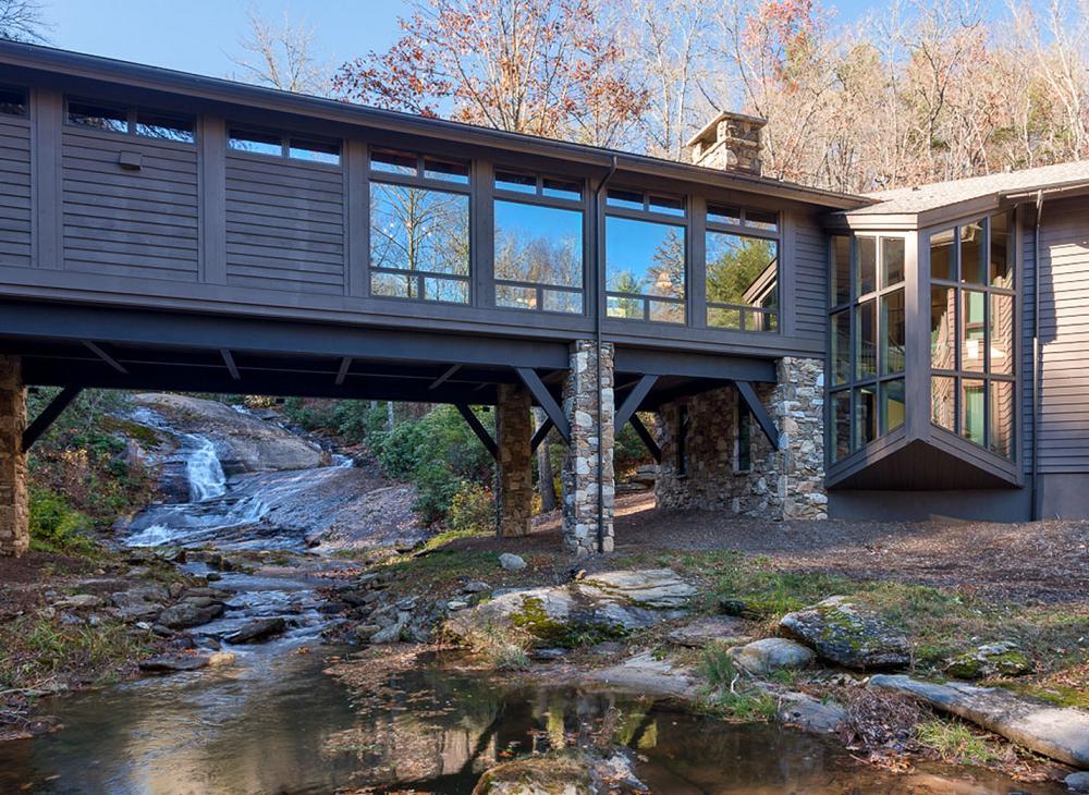 Casa din piatra naturala si placata cu lemn, construita peste un parau de munte