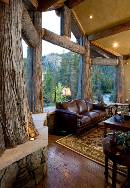 Living cu perete cu trunchiuri de copaci in care sticla a fost incastrata direct