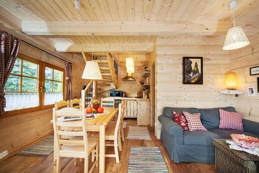 Zona de zi cu peretii si dusumelele din lemn ale unei case din busteni rotunzi