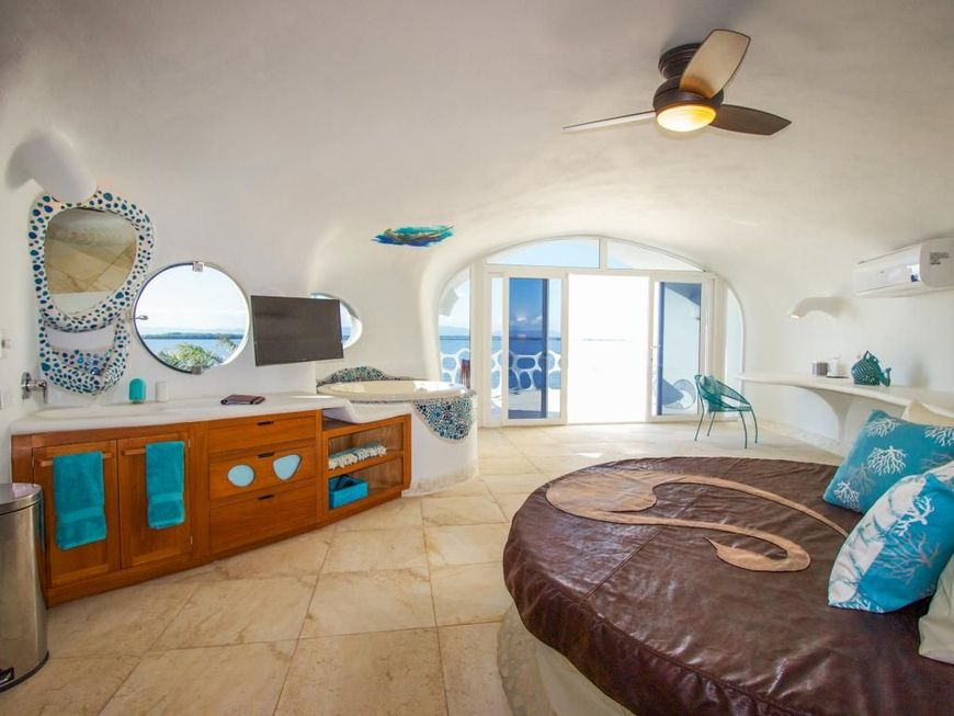 Pat rotund in dormitorul cu baie al unei case cu arhitectura organica construita pe malul marii