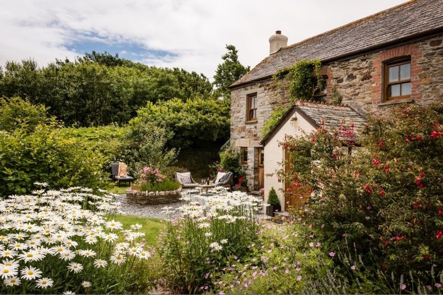 Gradina rustica cu flori a unei case din piatra