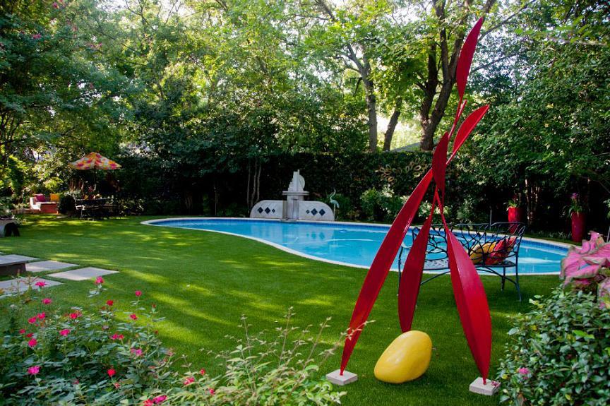 O frumoasa gradina cu obiecte de decor colorate si o piscina cu linii curbe
