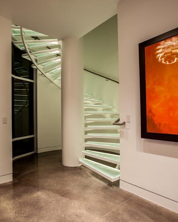 Scara interioara spiralata moderna, cu trepte din sticla si schelet metalic