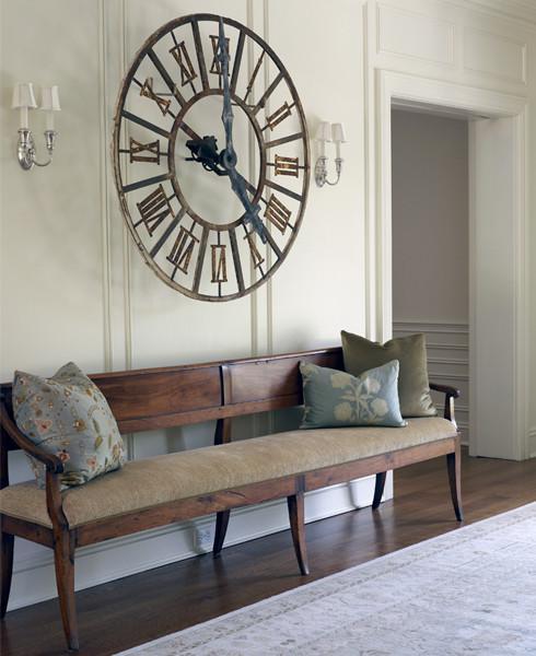 Un decor simplu in care accentul cade pe bancuta din lemn si ceasul de perete de deasupra
