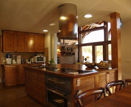 Poze Bucatarie - Insula din lemn din bucatarie inglobeaza chiuveta, cuptorul, plita de gatit