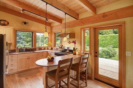 Poze Bucatarie - Culori calde, materiale naturale si multa lumina in bucataria deschisa a unei mici case din lemn
