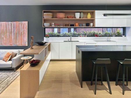 Poze Bucatarie - Un element de design original al acestei bucatarii moderne este luminatorul incastrat din zona de gatit