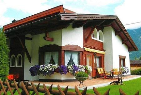 Poze Fatade - O casa frumoasa cu finisaje din lemn ce decoreaza acoperisul, geamurile si o parte a fatadei