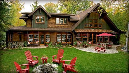 Poze Case lemn - Casa din lemn cu o curte verde si fotolii rosii in jurul vatrei de foc
