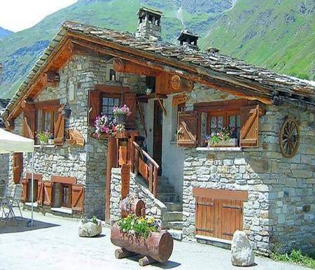 Casa din piatra cu obloane din lemn intr un decor montan for Casa la tara ieftina