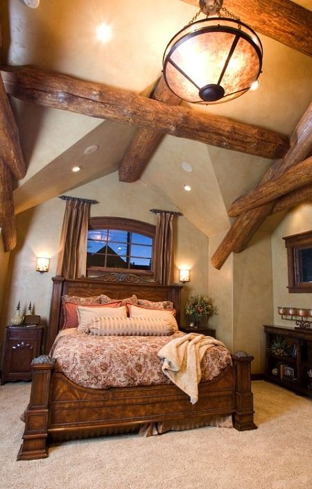 Dormitor amenajat in stil rustic, cu patul si grinzile din lemn masiv, la vedere