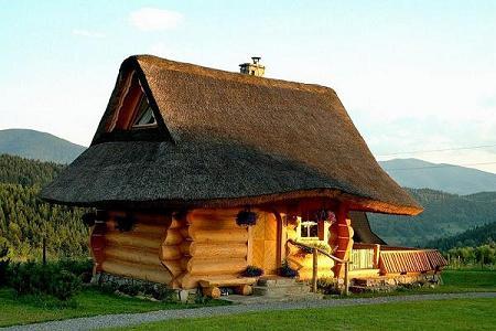 Poze Case lemn - Casa construita din busteni rotunzi cu acoperis din stuf ce pare desprinsa din lumea povestilor
