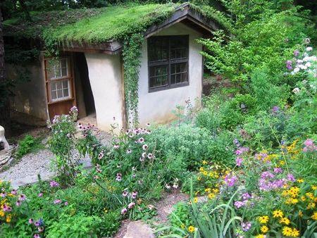 Poze Casute de gradina - Casuta de gradina ecologica intr-o mare de flori. Casuta este construita din materiale ecologice: baloti de baie, lut, lemn avand si un acoperis verde
