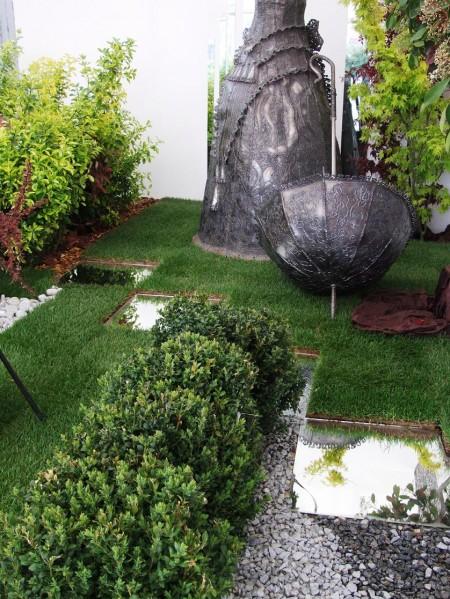 Poze Gradina de flori - Stand expozitional amenajat cu gazon, arbusti, plante de exterior, pietre, decor din fier forjat, zone acvatice