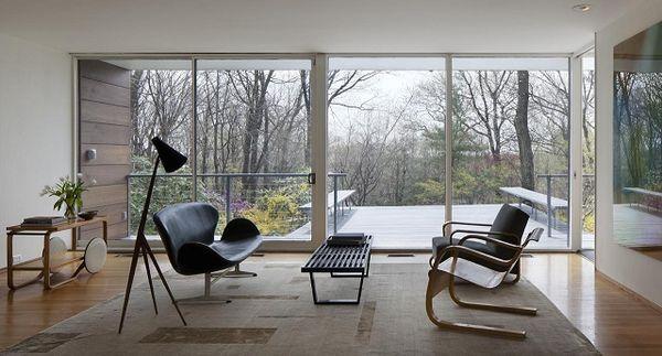 Living cu pereti de sticla care conecteaza interiorul cu padurea din jur