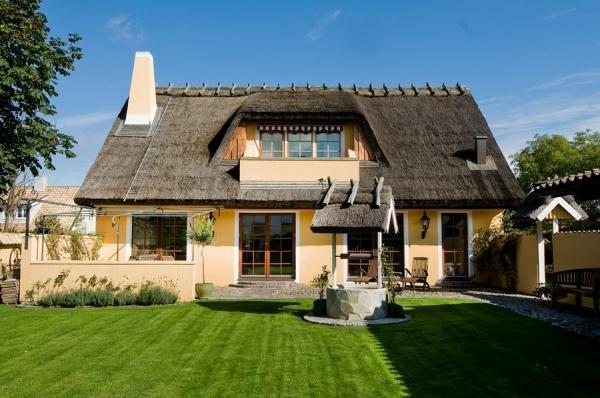 O casa ca-n povesti: acoperis din stuf, gard de piatra, poarta din fier forjat si o curte acoperita cu piatra naturala si iarba