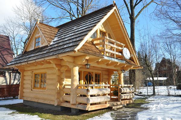Casa din busteni rotunzi si semirotunzi cu pridvor si dormitoare la mansarda